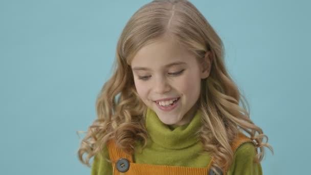 Portrét krásné mladé dívky, která se usmívá na kameru izolované přes modré pozadí