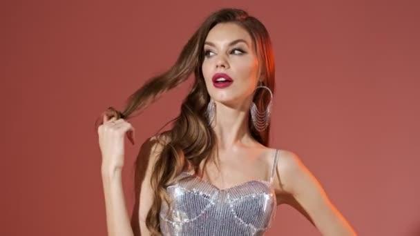 Záhada hezká žena v jasných flitry šaty hrát s vlasy a při pohledu na kameru přes červené pozadí