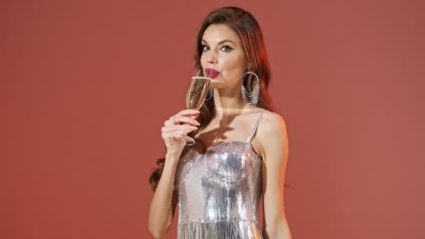 Glückliche hübsche Frau im hellen Paillettenkleid, Champagner trinkend und vor rotem Hintergrund in die Kamera blickend