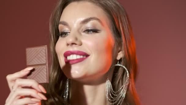 Nahaufnahme von erfreut hübsche Frau in hellen Pailletten Kleid Schokolade essen und genießen den Moment über rotem Hintergrund