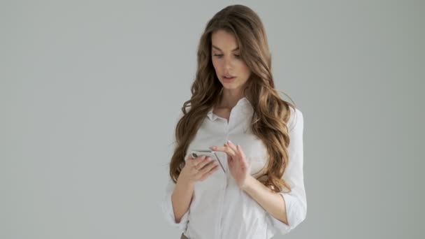 Eine schöne Frau winkt jemandem zu, während sie ihr Smartphone isoliert vor grauem Hintergrund im Studio benutzt
