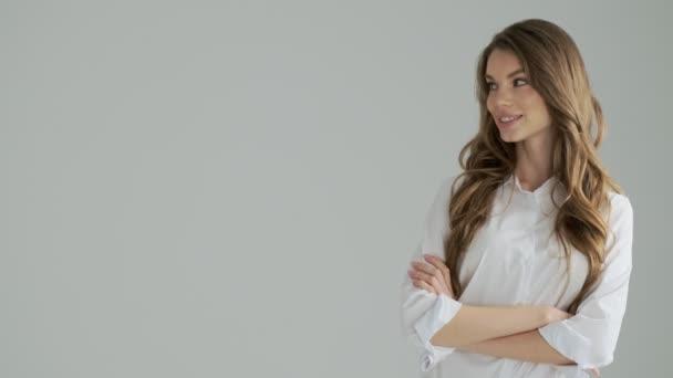 Eine zufrieden lächelnde Frau blickt zur Seite und zwinkert isoliert über einen grauen Hintergrund im Studio