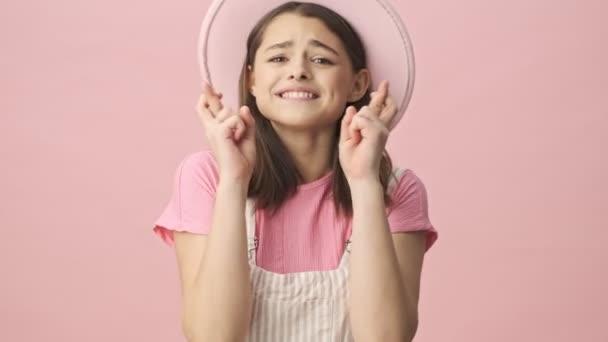 Konzentrierte hübsche brünette Frau in Overalls und Hut, die mit erhobenen Daumen betet und vor rosa Hintergrund in die Kamera schaut