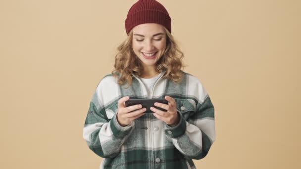 Fröhliche hübsche Frau mit Strickmütze und Hemd spielt auf Smartphone vor beigem Hintergrund