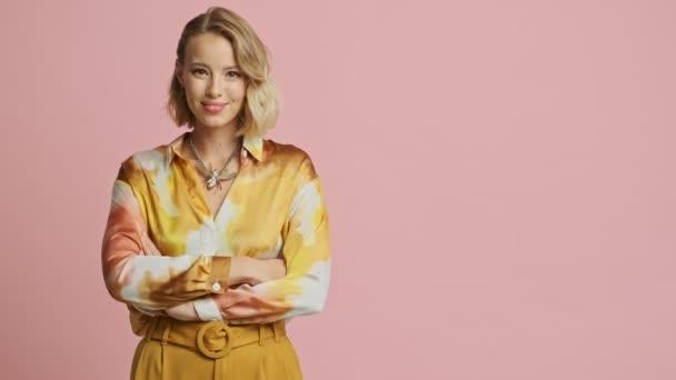 Boldog szép szőke nő színes elegáns jelmez mutatva a copyspace és mutatja hüvelykujját fel rózsaszín háttér