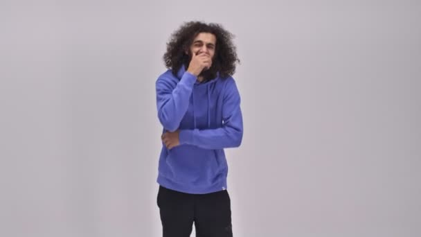 An emotional affectionate young bearded brunette man with long curly hair is laughing out loud over the gray wall in the studio