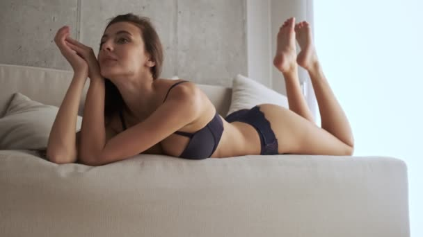 Usmívající se hezká brunetka žena ve spodním prádle dívá pryč, zatímco leží na pohovce doma