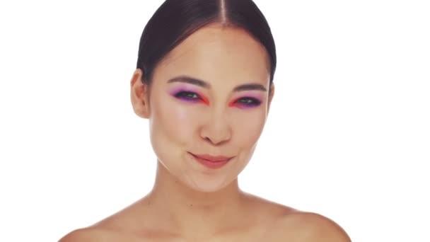 Atraktivní polonahá asijská žena s jasnou módní oční make-up ukazuje různé emoce do kamery izolované přes bílé pozadí ve studiu
