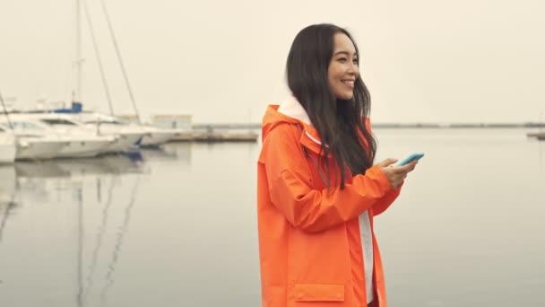 Attraktive asiatische fröhliche Frau, die im orangefarbenen Mantel am Hafen vorbeiläuft, plaudert mit dem Handy.
