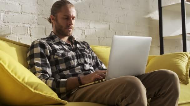 Egy komoly koncentrált férfi gépel a laptopján, otthon ül a nappaliban.