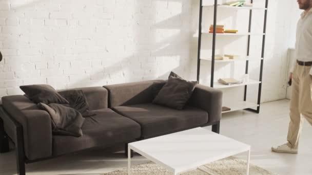 Ein gutaussehender junger Mann geht und liegt zu Hause auf dem Sofa im Wohnzimmer