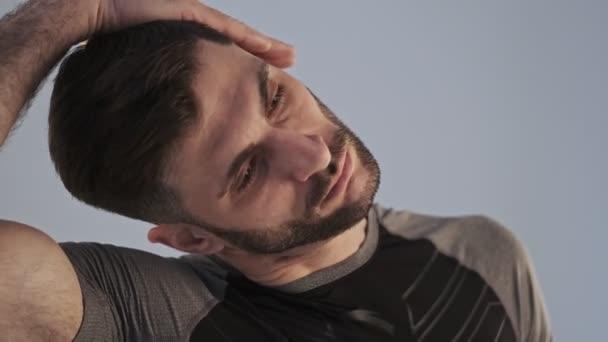 Klidný mladý atletický muž ve sportovním oblečení dělá cvičení protáhnout krk před cvičením izolované přes šedé pozadí ve studiu