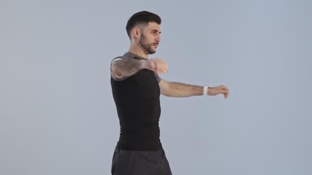 Soustředěný mladý atletický muž ve sportovním oblečení provádí zahřívací cvičení izolované nad šedým pozadím ve studiu