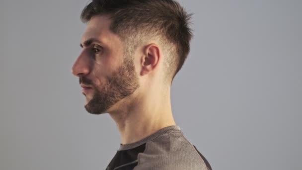 Boční pohled na seriózního sportovního mladíka ve sportovním oblečení otáčí hlavu ke kameře izolované přes šedé pozadí ve studiu