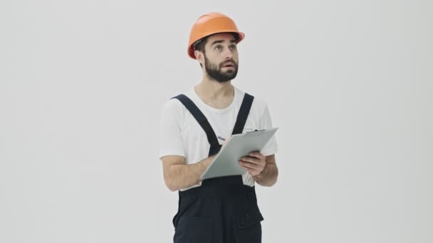 Concentrated young bearded man builder isolated over white wall background in helmet writing notes in clipboard.