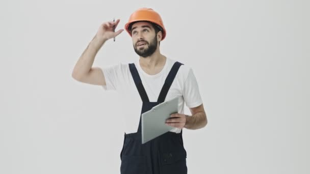 Thoughtful young bearded man builder isolated over white wall background in helmet writing notes in clipboard.