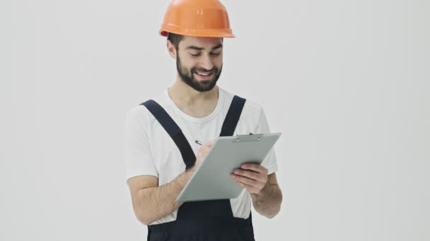 Cheery positive young bearded man builder isolated over white wall background in helmet writing notes in clipboard.