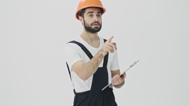 Fröhlich konzentrierter junger bärtiger Bauarbeiter isoliert über weißem Wandhintergrund in Helmschrift Notizen in Klemmbrett.