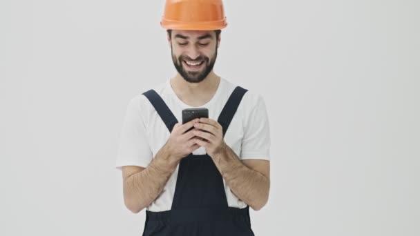 Šťastný pozitivní mladý vousatý muž stavitel izolované přes bílou zeď pozadí v helmě pomocí mobilního telefonu
