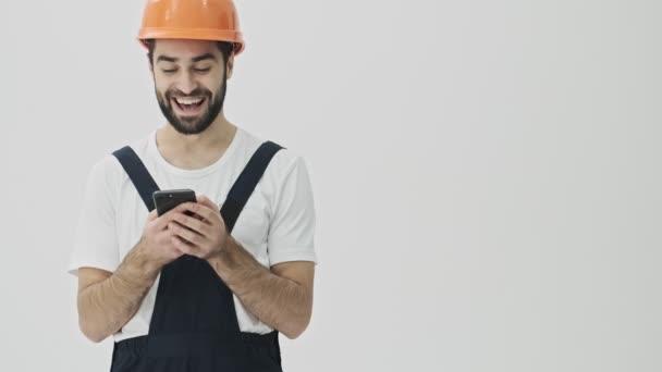 Pozitív vidám fiatal szakállas férfi építész elszigetelt fehér fal háttér sisak segítségével mobiltelefon.