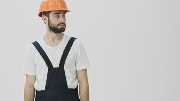 Pozitivní mladý vousatý muž stavitel izolované přes bílou zeď pozadí v helmě ukazuje stranou.