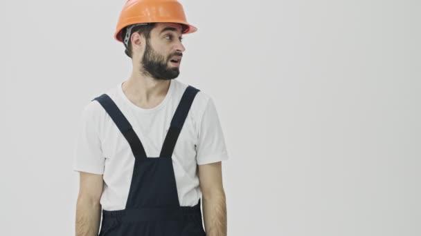 Zmatený mladý vousatý muž stavitel izolované přes bílou zeď pozadí v helmě ukazuje stranou.