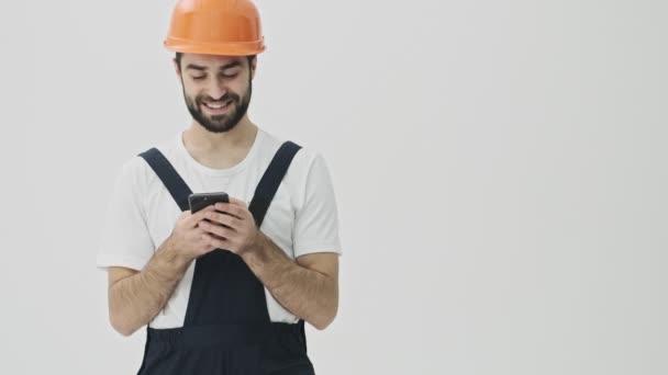 Positive junge bärtige Mann Bauarbeiter isoliert über weiße Wand Hintergrund in Helm zeigt zur Seite mit Handy