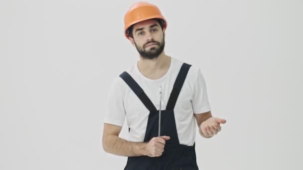 Soustředěný mladý vousatý muž stavitel izolované přes bílou zeď pozadí v helmě s klíčem