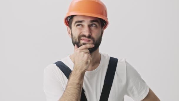 Myslet mladý vousatý muž stavitel izolované přes bílou zeď pozadí v helmě
