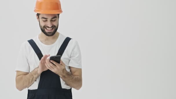 Positive cheerful young bearded man builder isolated over white wall background in helmet showing display of mobile phone and thumbs up.