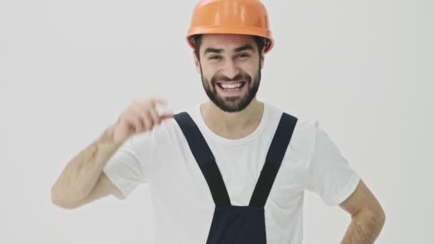 Boldog pozitív fiatal szakállas férfi építész elszigetelt fehér fal háttér sisak