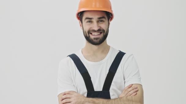 Šťastný úsměv optimistický mladý vousatý muž stavitel izolované přes bílou zeď pozadí v helmě ukazující palce nahoru