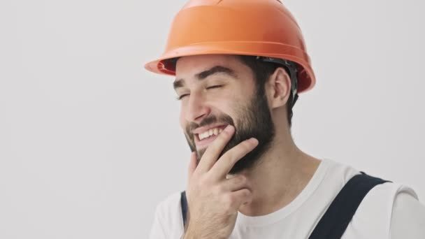 Dreaming happy young bearded man builder isolated over white wall background in helmet