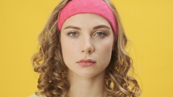 Eine ziemlich ruhige junge athletische Frau in Sportbekleidung blickt isoliert vor einem gelben Hintergrund im Studio in die Kamera.