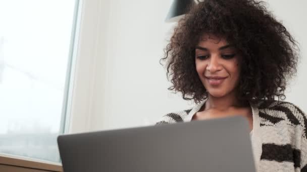 Fiatal pozitív pihentető afrikai göndör nő otthon segítségével laptop számítógép
