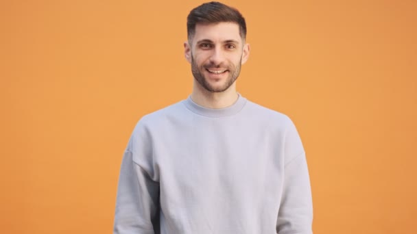 Young optimistic pleased man isolated over yellow wall background
