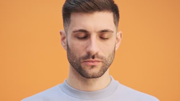 Mladý seriózní muž izolované přes žlutou zeď pozadí