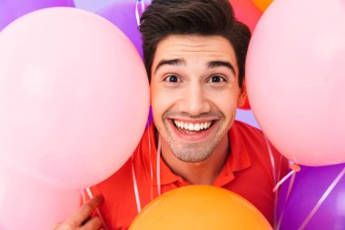 Image closeup of happy delighted man rejoicing while posing in multicolored air balloons isolated over violet background