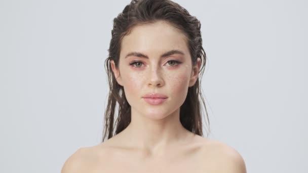 Egy nyugodt, fiatal, félmeztelen nő, nedves hajjal, kinyitja a szemét, és a kamerába néz, elszigetelve egy világoskék háttérrel a stúdióban.