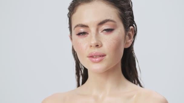 Okouzlující mladá polonahá žena s mokrými vlasy je pózování při dotyku její tvář izolované přes světle modré pozadí ve studiu