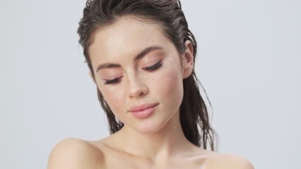 Nádherná mladá polonahá žena s mokrými vlasy představuje izolované přes světle modré pozadí ve studiu