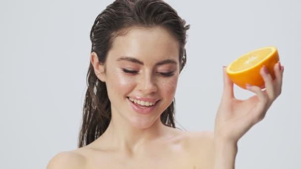 Atraktivní mladá polonahá žena s mokrými vlasy pózuje s pomerančovým ovocem izolovaným přes světle modré pozadí ve studiu