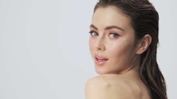 Okouzlující mladá polonahá žena s mokrými vlasy pózuje a mrká, zatímco otáčí hlavu ke kameře izolované přes světle modré pozadí ve studiu