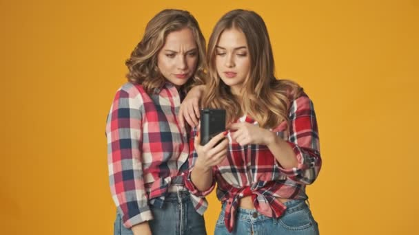 Mladý pozitivní šťastný hezké dívky izolované přes žluté stěny pozadí pomocí mobilního telefonu