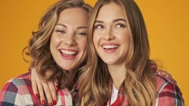 Mladé dívky šťastný přátelé sestry izolované přes žlutou zeď pozadí objímání
