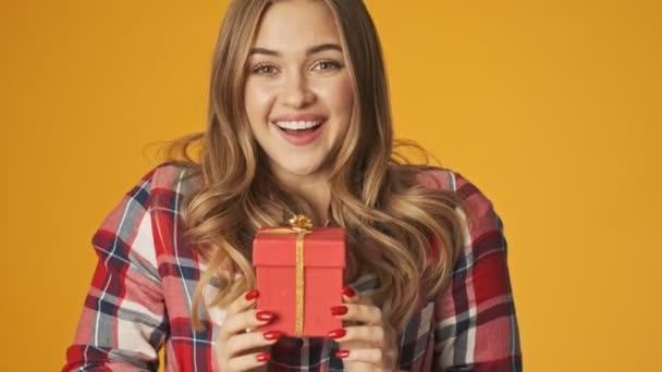 Mladý šťastný pozitivní dívka izolované přes žlutou zeď pozadí vám dává dárek box