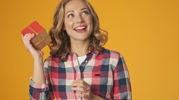 Mladá veselá dívka izolované přes žlutou zeď pozadí držení současné krabice se snaží hádat, co je uvnitř
