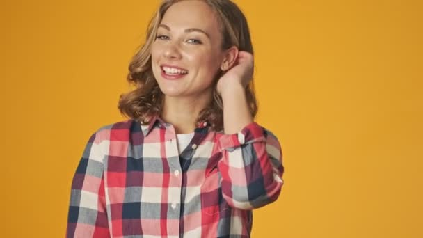 Young happy optimistic girl isolated over yellow wall background