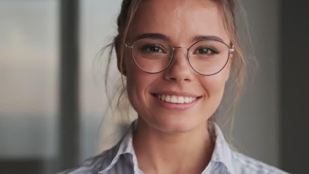 Egy közeli kép egy barátságos, mosolygós, szemüveges fiatal nőről, aki otthon a kamerába néz.