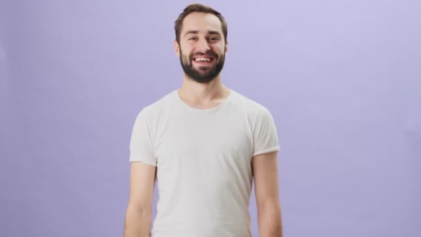 An attractive young man wearing white t-shirt is showing thumb up gesture while standing isolated over gray background